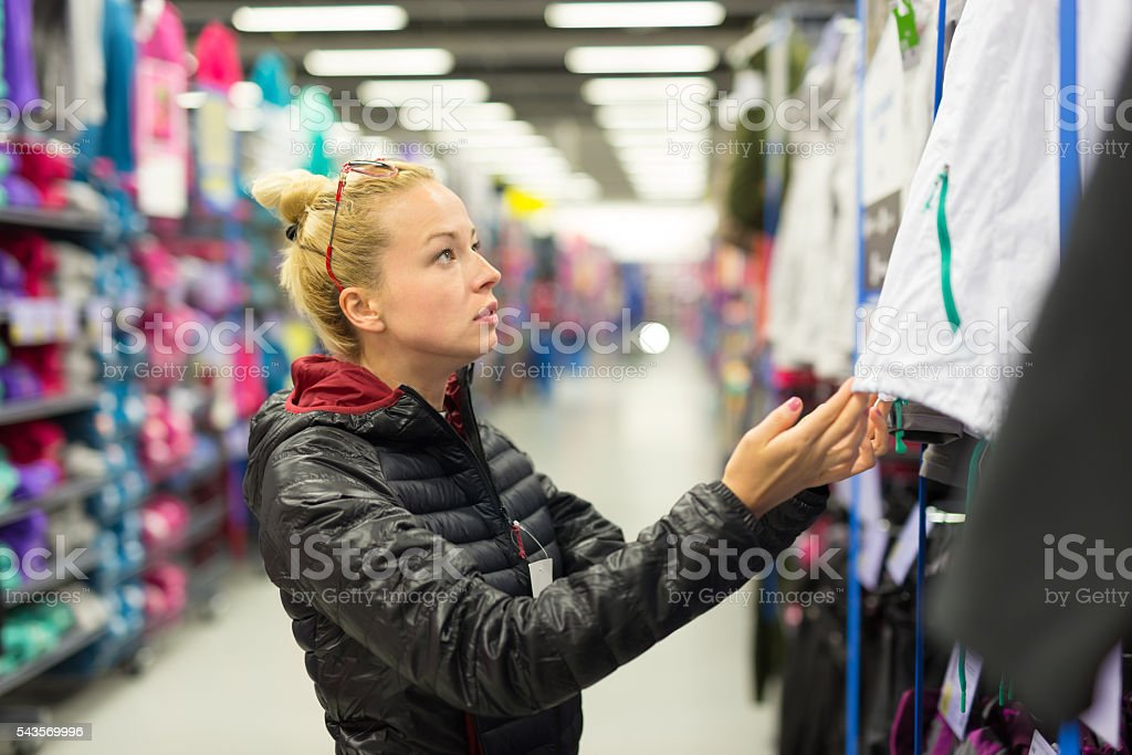 Woman shopping sportswear in sports store. – Foto