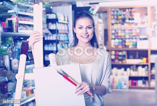594918592 istock photo woman shopping wooden easel 583732220