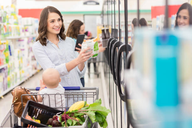 woman shops for frozen vegetables in a supermarket - happy person buy appliances stock photos and pictures