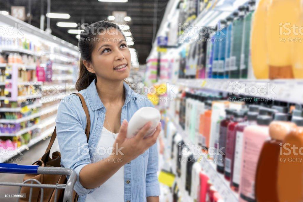 Woman shops for shampoo in supermarket - Foto stock royalty-free di Abbigliamento casual