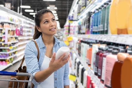 Woman Shops For Shampoo In Supermarket - Fotografie stock e altre immagini di Abbigliamento casual