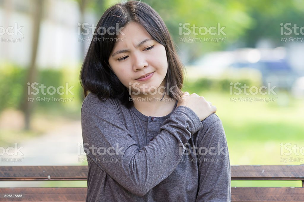 Woman: Shoulder Pain at Park stock photo
