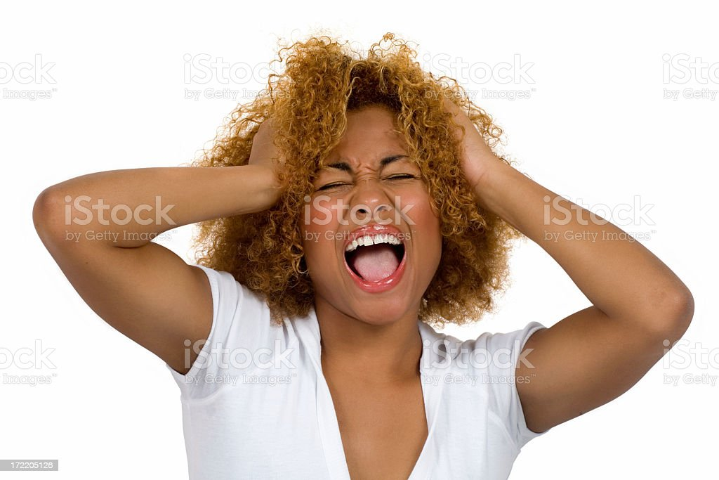 A woman shouting while clutching her hair and squinting royalty-free stock photo