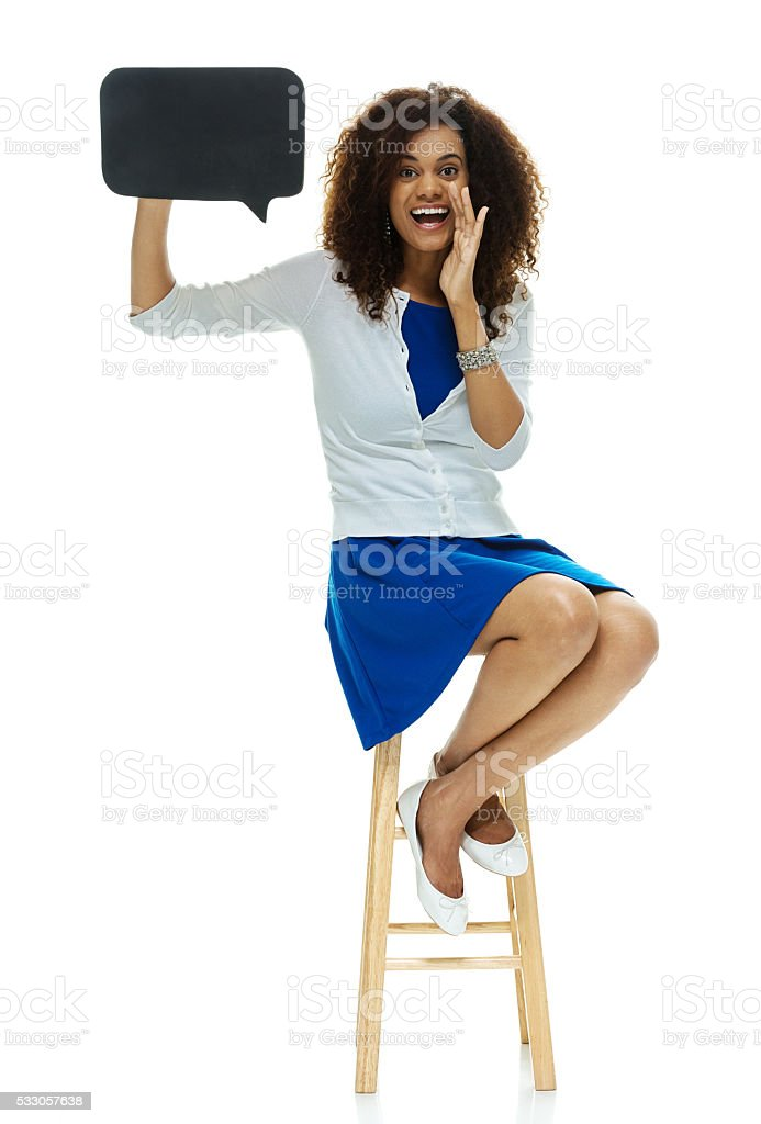 Woman shouting while holding speech bubble stock photo