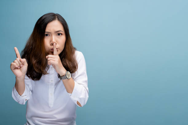 Woman show a quiet sign isolated over blue background stock photo
