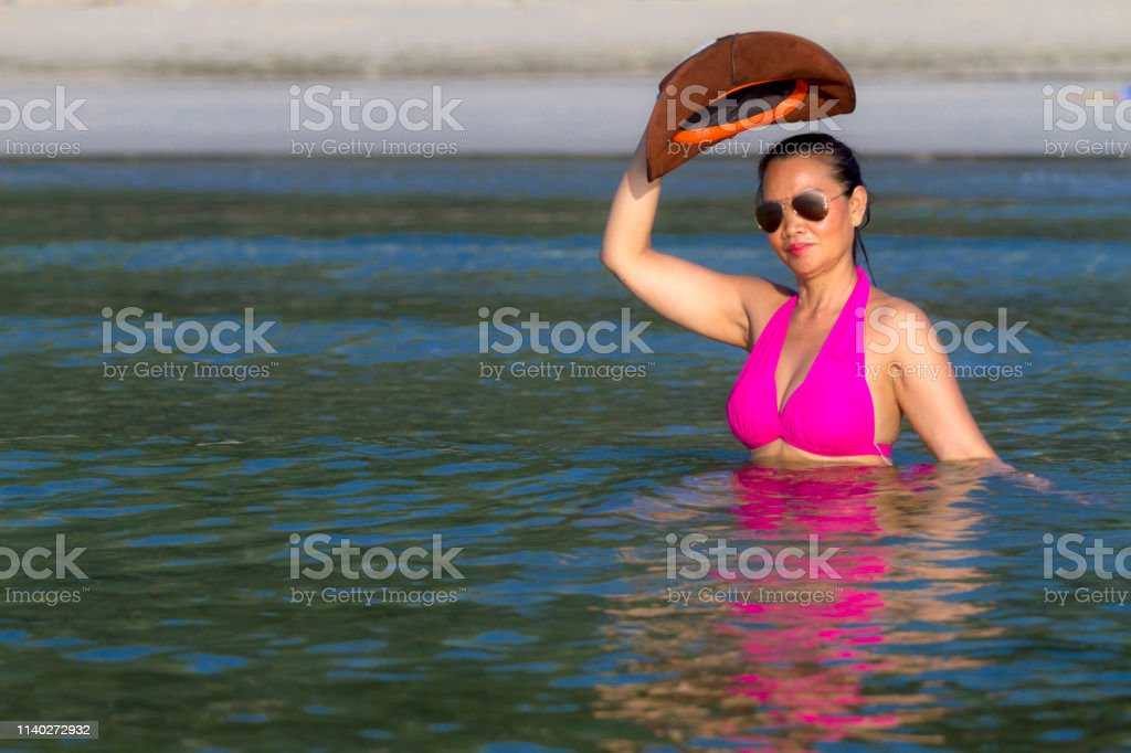 Woman show bikini pink and hat on beach at Thung Wua Laen Beach,...