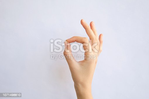 Young woman hand isolated on gray.