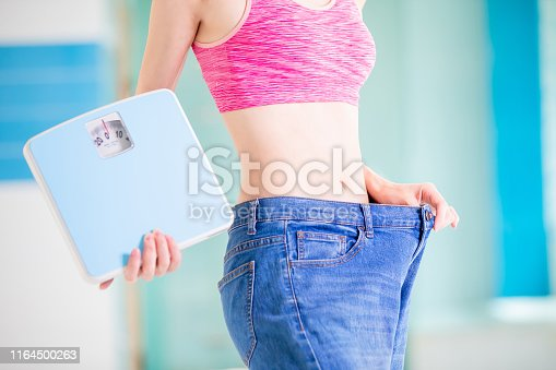 521792753istockphoto woman show her big jeans 1164500263