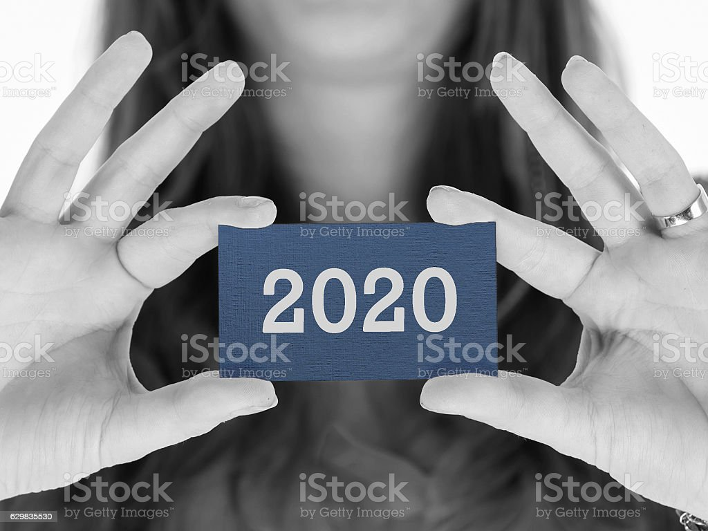 Woman showing a business card - 2020 stock photo
