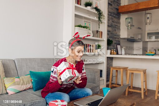 Mid adult woman showing a Christmas gift to someone online.