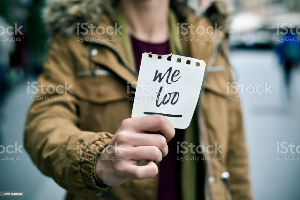 woman showing a note with the text me too closeup of a young caucasian woman in the street showing a piece of paper with the text me too written in it Abuse Stock Photo