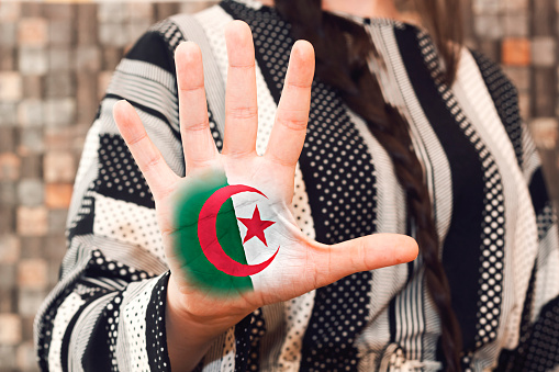 woman showing algeria flag painted on  open palm hand