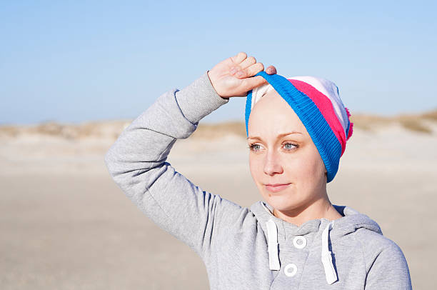 woman showing bald head - secondary effect of chemotherapy stock photo
