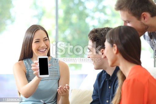 istock Woman showing blank phone screen to her friends 1133988067