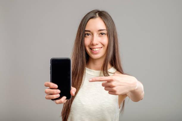 空のスマートフォンの画面を示す女性 ストックフォト