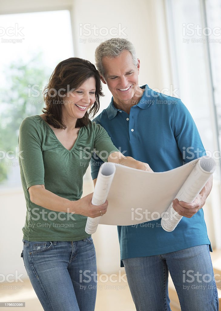 Woman Showing Blueprint To Husband In New House stock photo