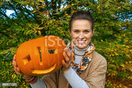 Trick or Treat. smiling modern woman on Halloween at the park showing carved pumpkin