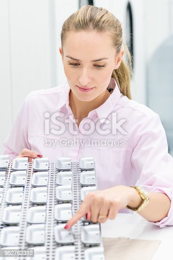 Vertical color image of woman showing metal merchandise on tray in factory.