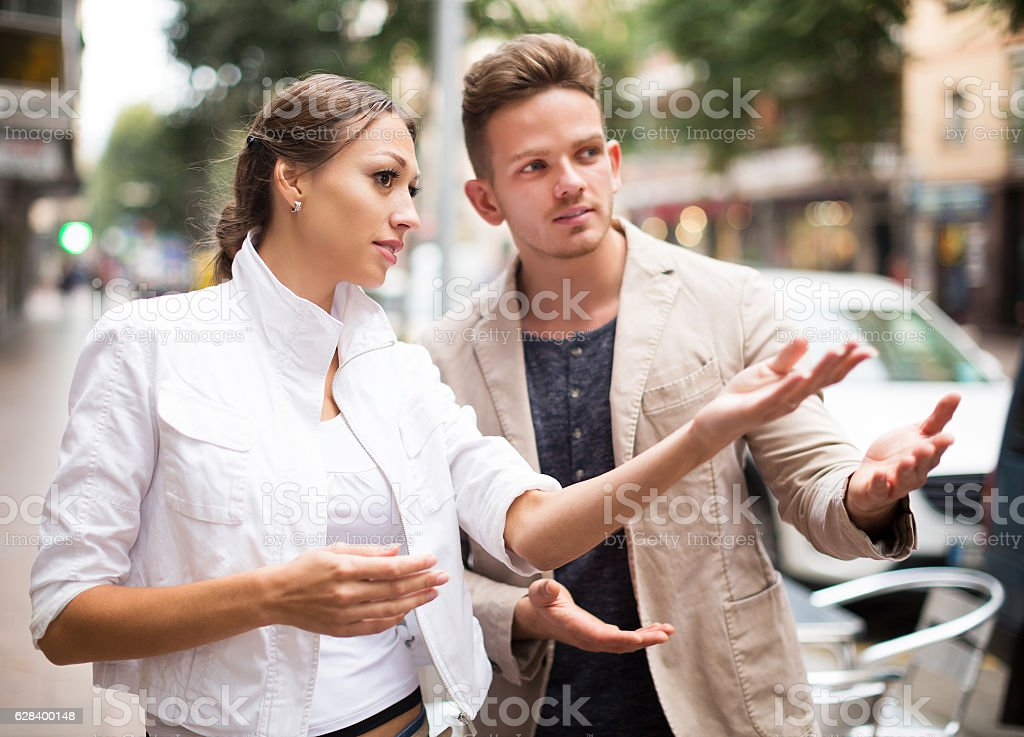 Woman showing direction to guy stock photo