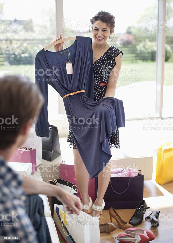 Woman showing dress to husband stock photo