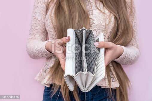 istock Woman showing empty wallet on pink background, closeup 957704170