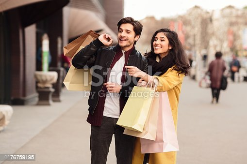 Wow, new shop. Woman showing fashion store, walking with husband after shopping