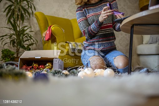 Adult woman showing gift box on a video call at her cosy living room.