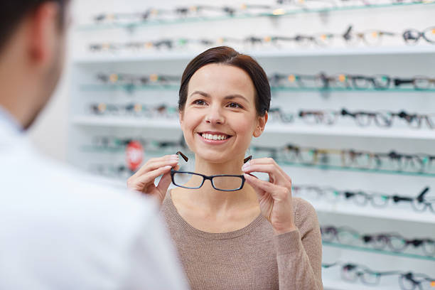 woman showing glasses to optician at optics store - sale lenses stock photos and pictures