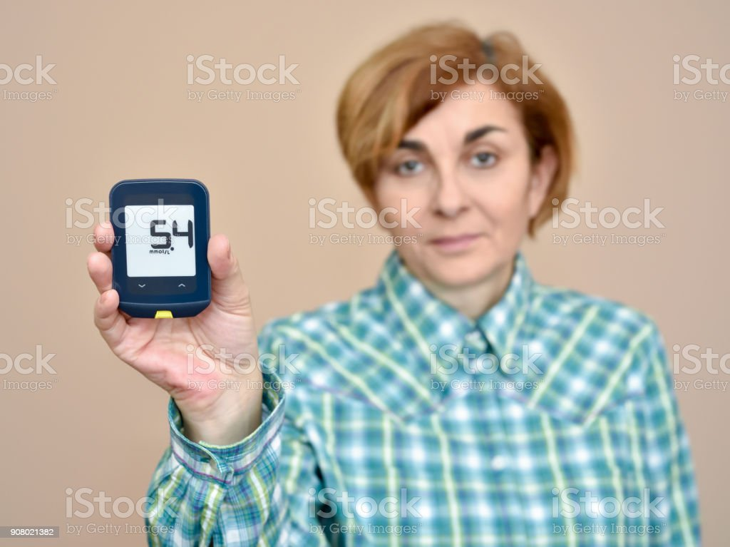 Woman showing glucose meter after measuring blood sugar stock photo