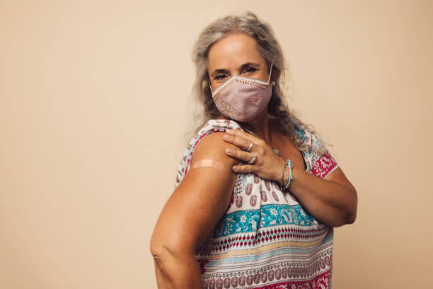 Woman showing her arm after getting vaccine stock photo