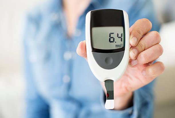 frau zeigt ihre glucose level-test. - blutzuckermessung stock-fotos und bilder