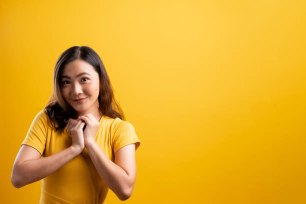 Woman showing her heartfelt gratitude on isolated yellow background stock photo