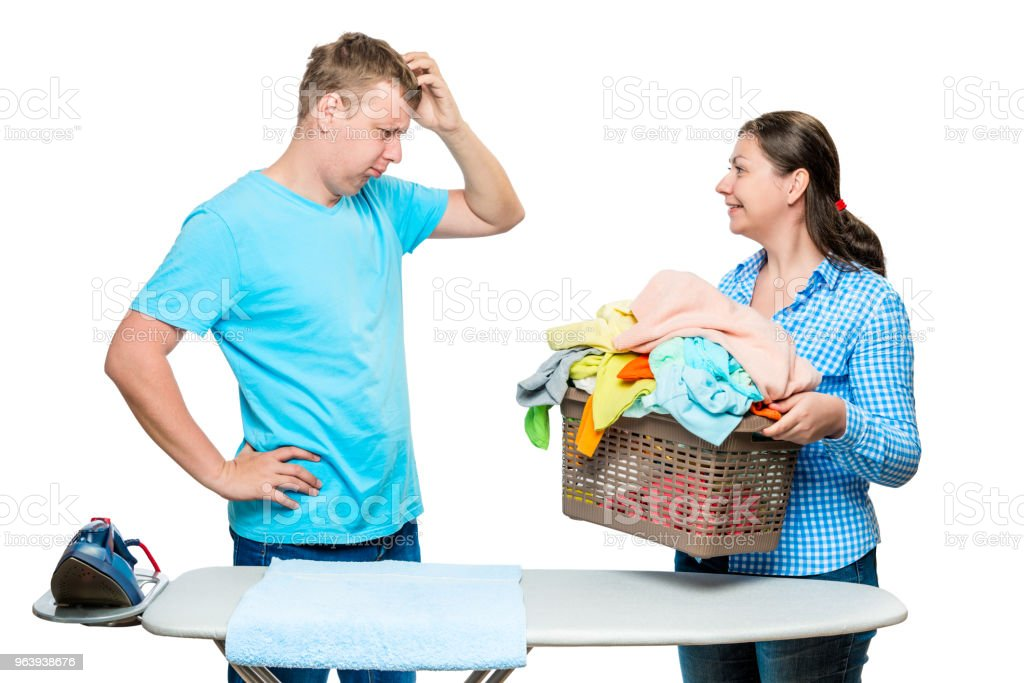 woman showing her husband a laundry cart for ironing, a portrait is isolated on a white background - Royalty-free Adult Stock Photo