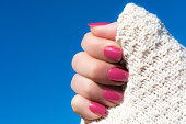 Woman showing her manicure against blue sky