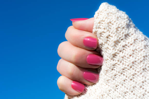Woman showing her manicure against blue sky Woman in a white knitted cardigan  showing her short pink manicure against blue sky pink nail polish stock pictures, royalty-free photos & images