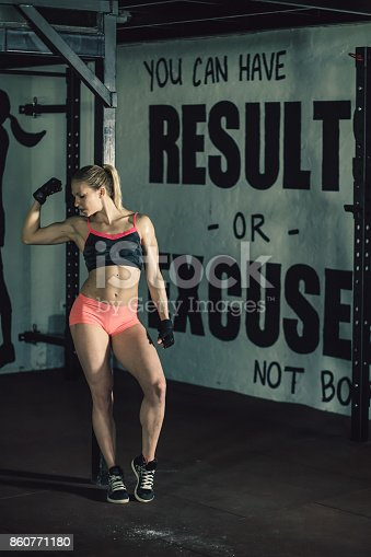 Woman showing her muscle after weightlifting.
