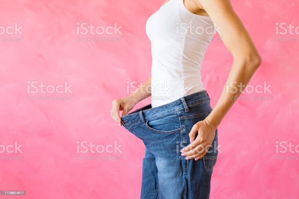 Woman showing her old big jeans after successful weight loss diet stock photo