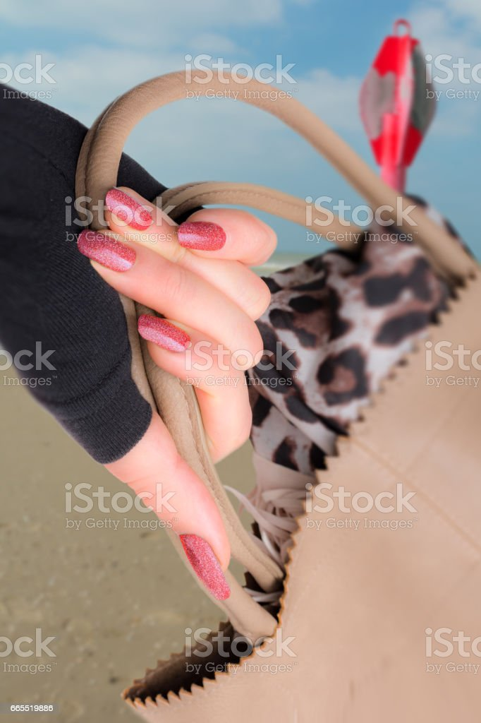 Woman showing her red glitter fingernails and taupe leather handbag on the beach - foto de stock