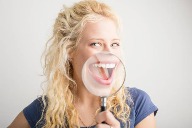 Woman showing her smile through magnifying glass stock photo