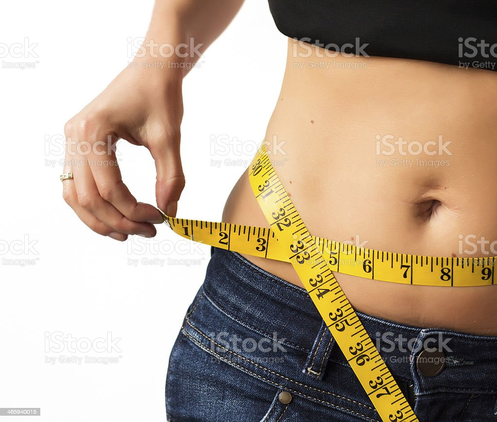 Woman showing her waist as she measures it stock photo