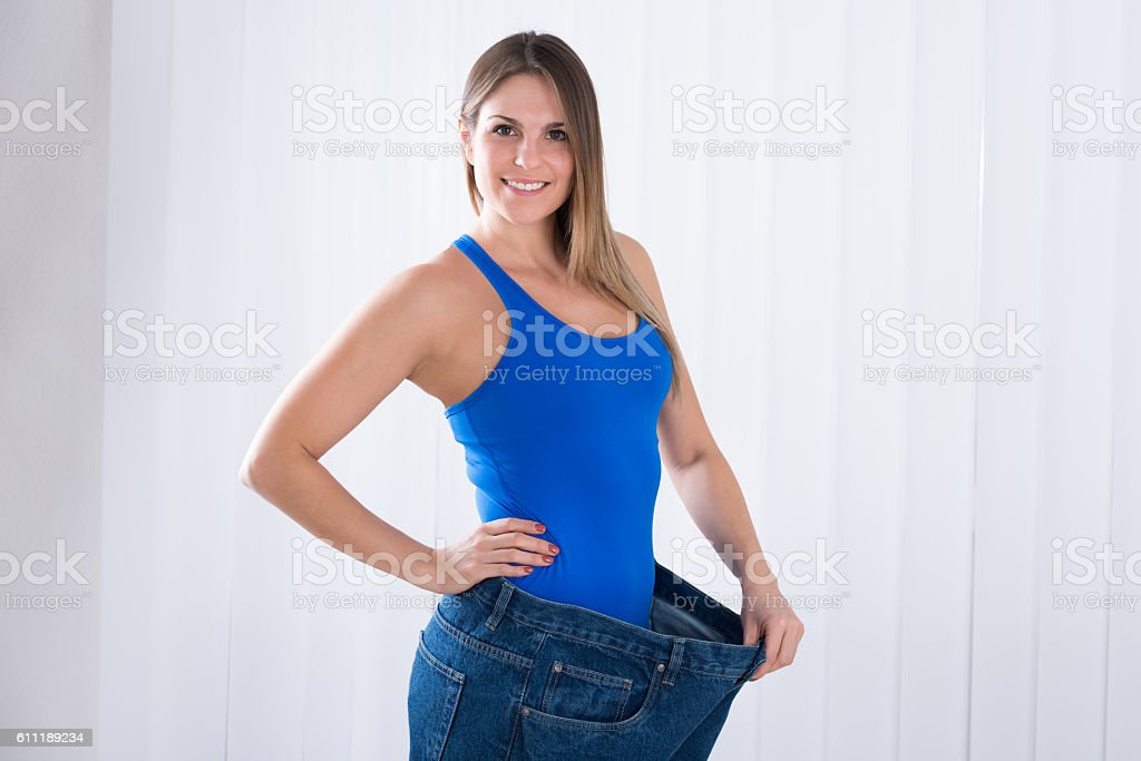 Woman Showing Her Weightloss By Wearing Jeans stock photo