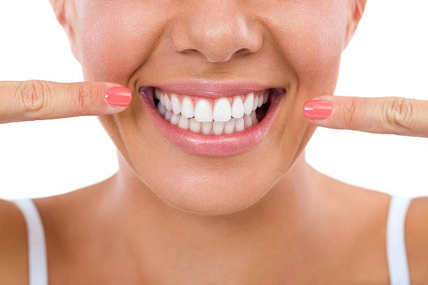 woman showing her white teeth. - teeth stock photos and pictures
