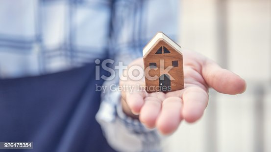 534196421istockphoto Woman showing house wood model with copy space, Home builder concept. 926475354