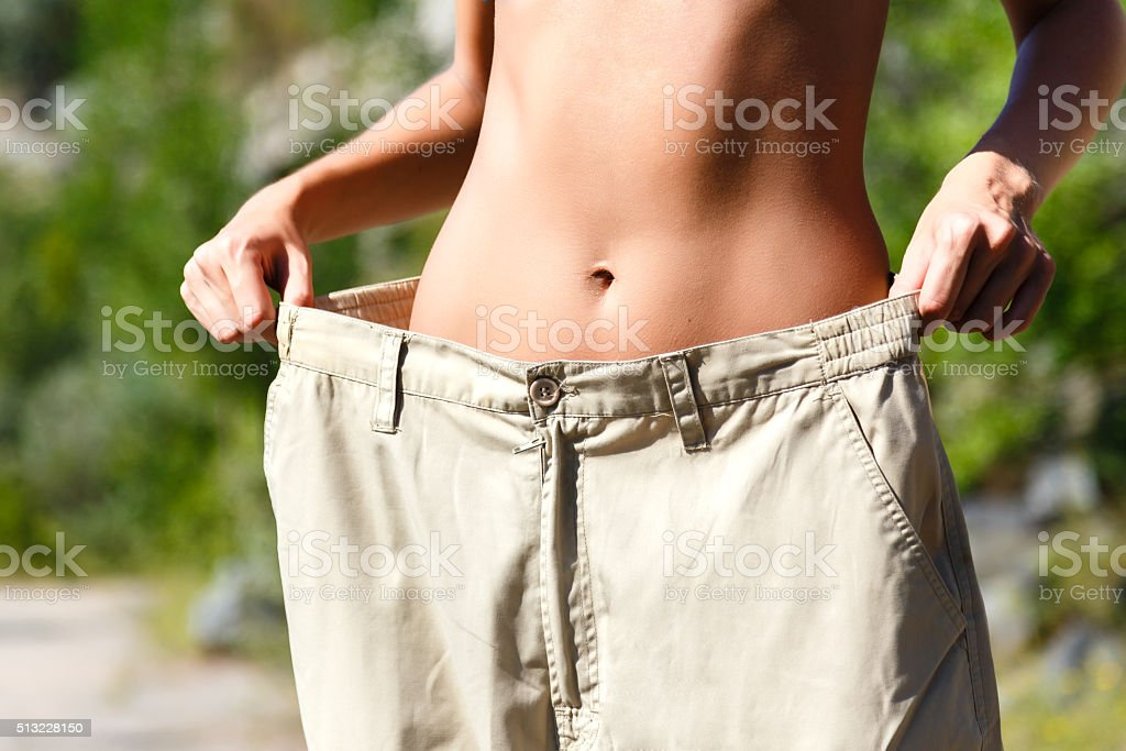 Woman showing how much weight she lost. stock photo