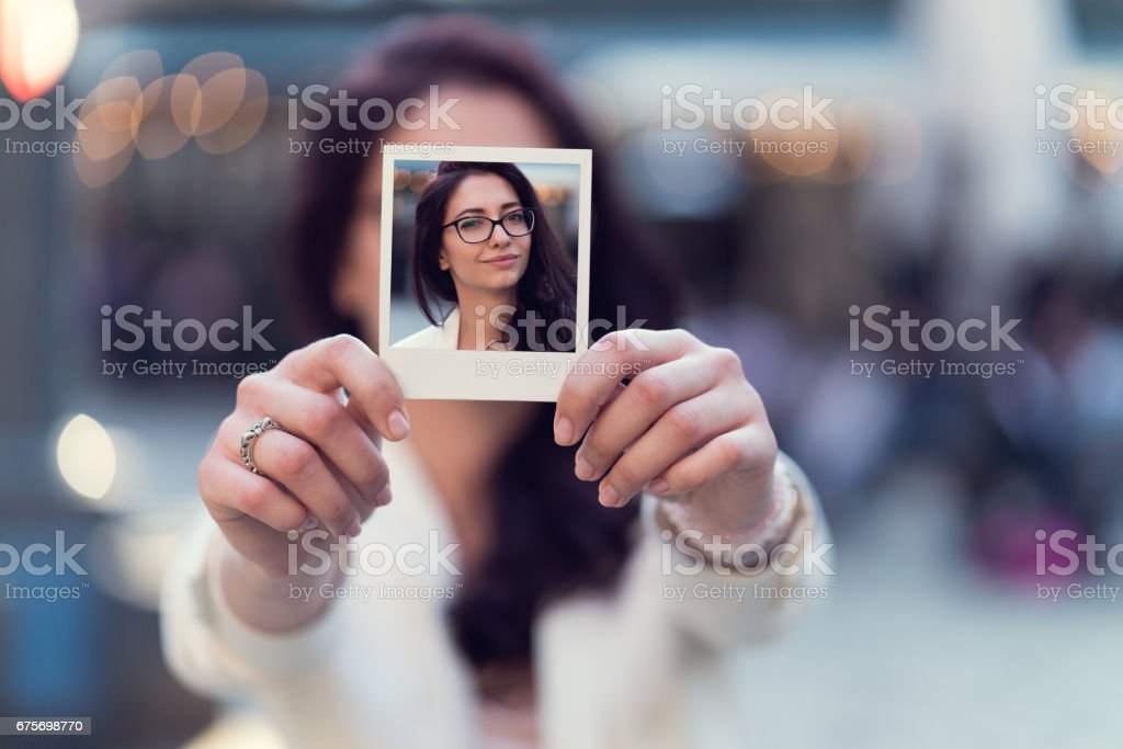 Woman showing instant photo to the camera royalty-free stock photo
