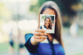 Young woman showing instant self portrait to the camera
