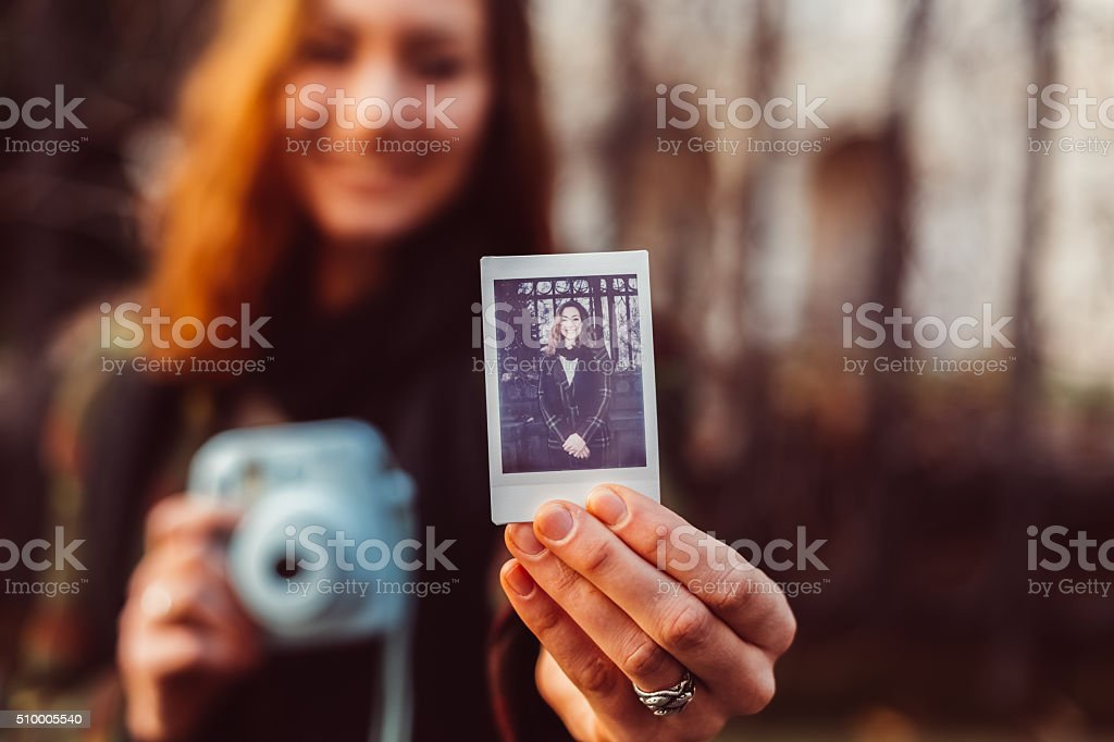 Woman showing instant selfie stock photo