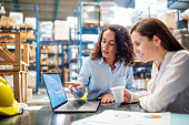 Young woman showing something on laptop to manager in factory warehouse. Two business women working together on laptop, checking the inventory.