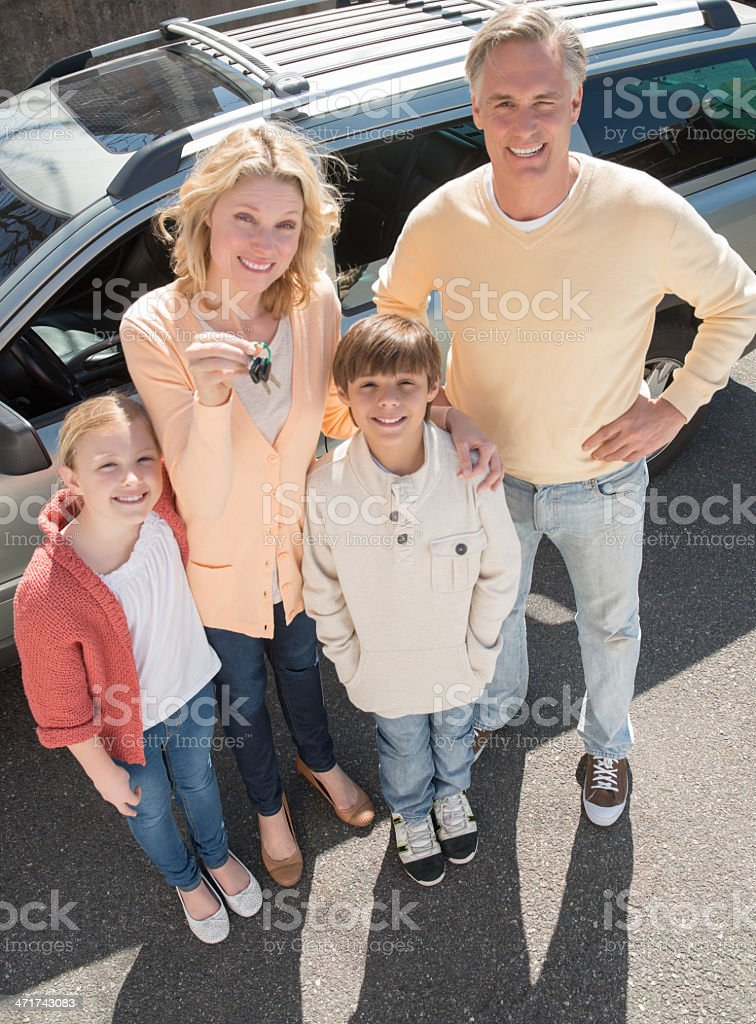 Woman Showing Keys While Standing With Family Against Car royalty-free stock photo