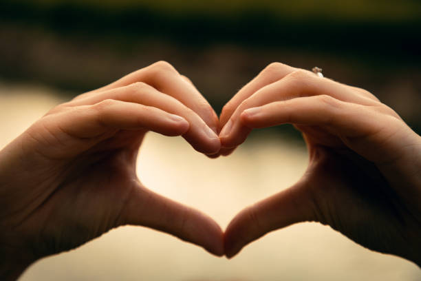 Woman showing Love Hand Sign Forming a Heart Sign stock photo